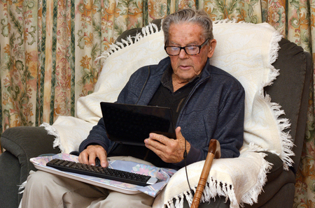 oldness: Old man 90s in eyeglasses working with laptop computer at home. Lifestyle concept technology, oldness, old age, retirement, family. Stock Photo