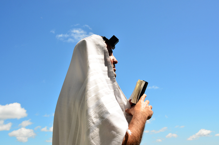 jewish background: An Jewish orthodox man prays with a blue sky background, reads a torah book (siddur) and wears, tefillin, tzitzit and tallit. Stock Photo