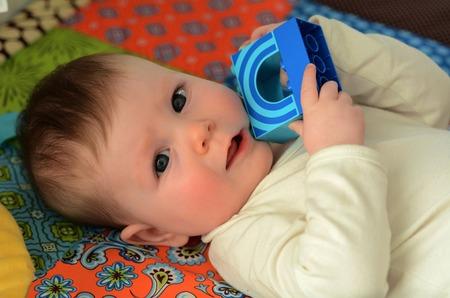 floor mat: Portrait of a baby awake on a baby floor mat. Stock Photo