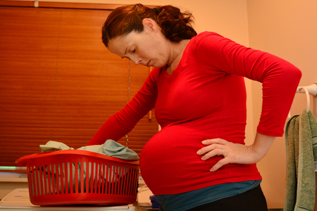 Pregnant housewife woman doing housework, washing family clothes, during pregnancy.Concept photo of pregnancy, pregnant woman lifestyle and health care. crop image - copy space
