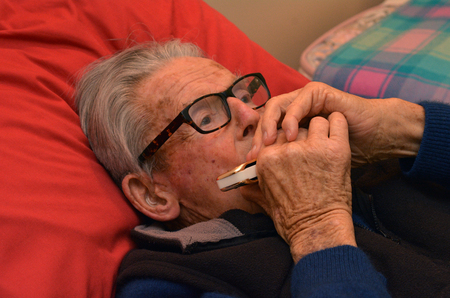 harmonica: Old man play harmonica in bed. Concept photo of old age, lonely, alone, retirement, music, sad. Stock Photo