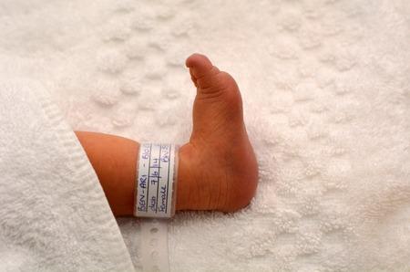 Newborn baby foot with identification bracelet tag name. Standard-Bild