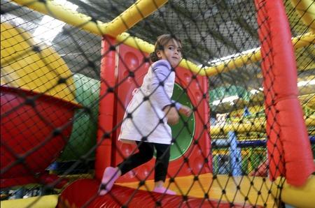 Juego de la niña en la zona infantil de juegos. Foto de archivo