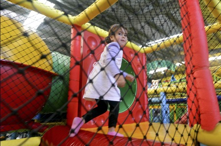 indoors: Little girl play in indoor playground.