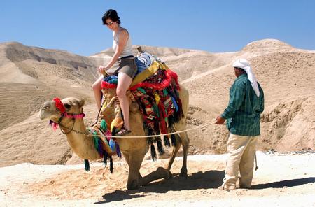 Tourist rides a camel of a bedouin man in the Judean Desert, Israel.