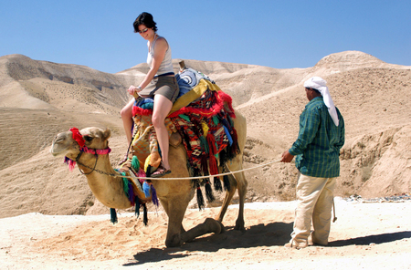 Tourist rides a camel of a bedouin man in the Judean Desert, Israel.