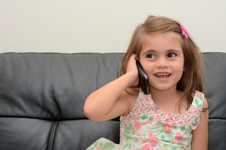 Happy little girl speak on the phone at home. Concept photo of long distance ,call ,communication, telephone, service, overseas, conversation, technology