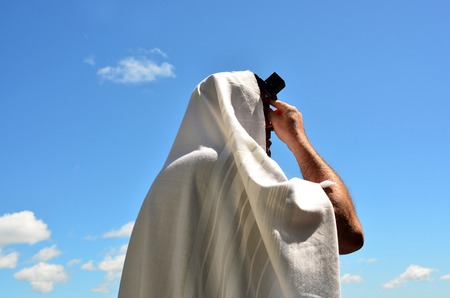 siddur: An Jewish orthodox man prays with a blue sky background, reads a torah book (siddur) and wears, tefillin, tzitzit and tallit. Stock Photo