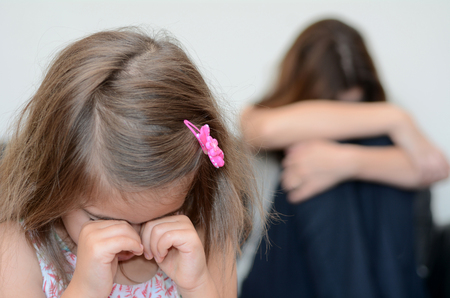 relationship mother and daughter: Little girl (age 05) cring with her desperate mother in background Stock Photo