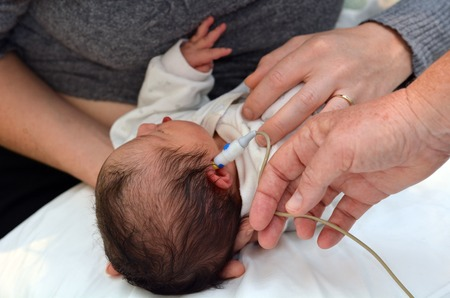 signal device: AUCKLAND - JUNE 09 2014:Newborn Infant (Naomi Ben-Ari age 0) during  hearing screening.Significant hearing loss is the most common disorder at birth. Approximately 1%-2% of newborns are affected.