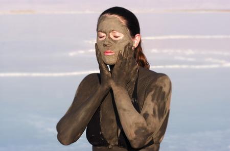 donna ricca: Una giovane donna in costume da bagno si sta godendo il fango minerale naturale proveniente dal Mar Morto, Israele.