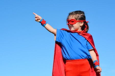 pretend: Superhero child (girl) points towards dramatic blue sky background with copy space. concept photo of Super hero, girl power, play pretend, childhood, imagination.