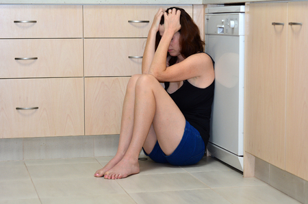 wife beater: Sad woman sit in her kitchen and covering her face after domestic violence