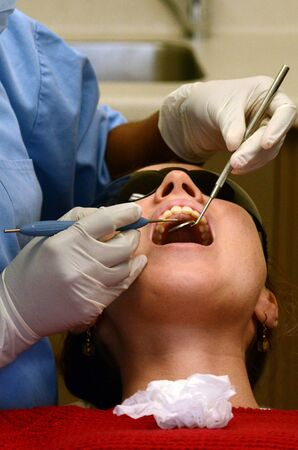 dental fear: KAITAIA, NZ - NOV 05:Female patient having her teeth examined by specialist dentist on Nov 05 2013.About 75% of US adults experiences dental fear. Up to 10% are considered to experience dental phobia. Stock Photo