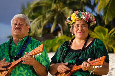 islanders: Portrait of two mature Polynesian Pacific islanders couple sing and plays Tahitian Music with Ukulele guitars on tropical beach with palm trees in the background. (Photo have MR)