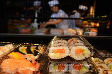food shop: Unrecognizable Japanese workers prepare Sushi rolls .
