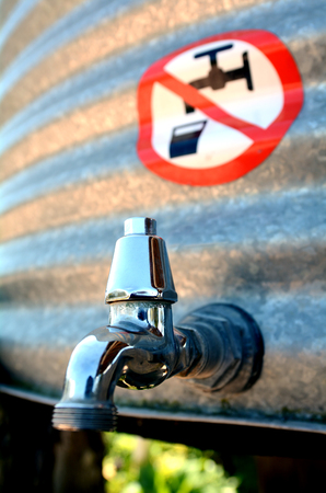 drinking water sign: Water forbidden to drink sign over outdoor water tank tap.