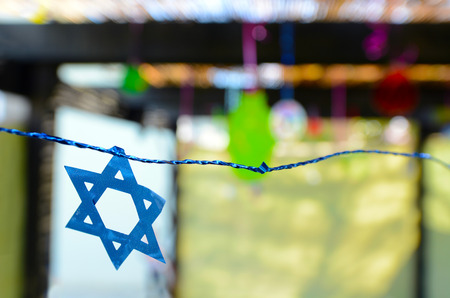 jewish star: Star of David decorations inside a Jewish family Sukkah for the Jewish festival of Sukkot. A Sukkah is a temporary structure where meals are taken for the week. Stock Photo