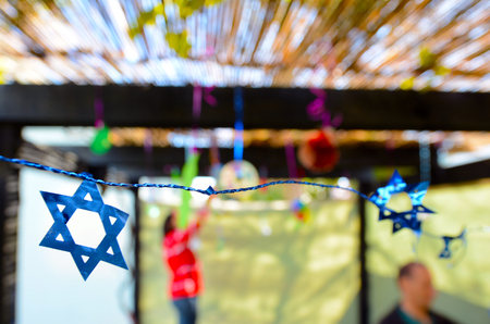 sukkoth festival: Jewish family decorating Sukkah for the Jewish festival of Sukkot. A Sukkah is a temporary structure where meals are taken for the week.