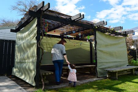 constraction: Jewish woman and child visiting their family Sukkah in the Jewish festival of Sukkot. A Sukkah is a temporary structure where meals are taken for the week.