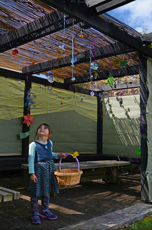 constraction: Jewish child (girl age 05) decorating her family Sukkah for the Jewish festival of Sukkot. A Sukkah is a temporary structure where meals are taken for the week. Stock Photo