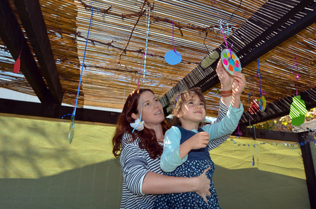 succos: Jewish woman and child decorating their family Sukkah for the Jewish festival of Sukkot. A Sukkah is a temporary structure where meals are taken for the week.