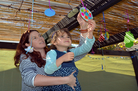 tabernacles: Jewish woman and child decorating their family Sukkah for the Jewish festival of Sukkot. A Sukkah is a temporary structure where meals are taken for the week.