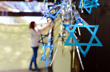 jewish star: Jewish woman decorating here family Sukkah for the Jewish festival of Sukkot. A Sukkah is a temporary structure where meals are taken for the week.
