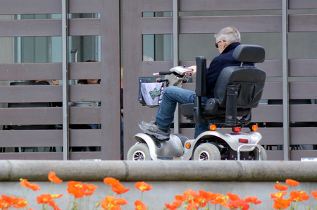 scooters: AUCKLAND,  NZL - OCT  01 2015:Elderly man drive mobility scooter.Currently the US Medicare will not approve a power wheelchair for persons who do not need to use the chair inside their own home.