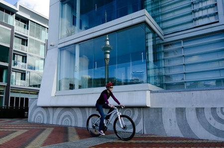 oficina antigua: AUCKLAND - 26 DE MAYO: paseo en bicicleta Mujer Auckland viaducto Basin Harbor el 26 de mayo un antiguo puerto comercial de 2013.It se convirti� en una promoci�n de pisos en su mayor�a de lujo, oficinas y restaurantes. Editorial
