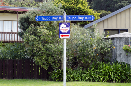 impacted: TAUPO BAY, NZ - MAY 11:Tsunami evacuation route sign on May 11 2011.NZ was hit by 15m high tsunami in the 15th Century and in last 150 years four tsunami events have impacted Northland east coast. Editorial