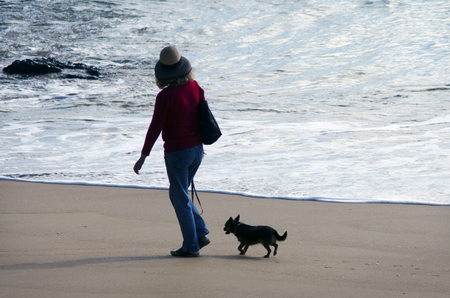 CABEL BAY, NZ - MAY 09:Woman dog owner walks her dog on May 09 2013.There are 475,072 dogs registered on the New Zealand National Dog Database.