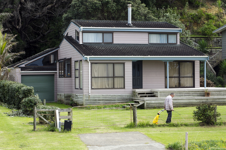 men at work: TAUPO BAY, NZ - MAY 11:Man carries a weedkiller sprayer spraying his home garden a on May 11 2011.New Zealand is among the countries experiencing a rapid rise in bed bug infestations.