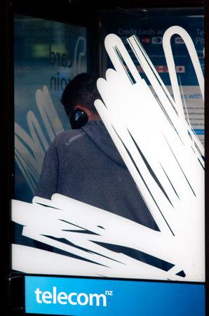 fixed line: AUCKLAND, Nueva Zelanda - 27 de mayo: Charla del hombre en un tel�fono p�blico de la calle el 27 de mayo de 2013.It un proveedor de servicios de comunicaciones de ancho NZ la prestaci�n de servicios de l�nea fija de tel�fono, red de telefon�a m�vil y servicios de Internet.
