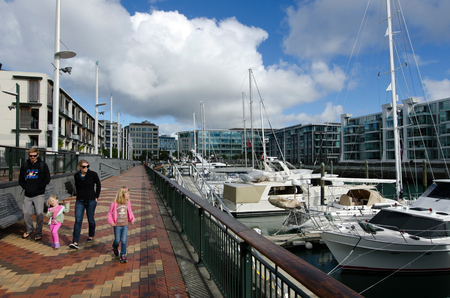 oficina antigua: AUCKLAND - MAY 26:Young family visit at Auckland Viaduct Harbor Basin on May 26 2013.Its a former commercial harbor turned into a development of  upscale apartments, office space and restaurants.