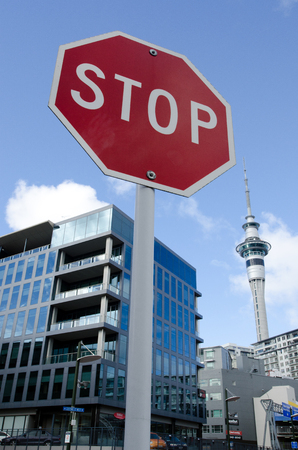 home prices: AUCKLAND, NZ - MAY 26: Stop sign under the Skytower on May 26 2013.House prices are booming around New Zealand - with the average price of an Auckland city home rocketing to $735,692