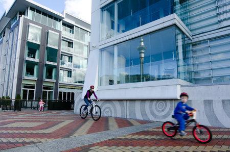 oficina antigua: AUCKLAND - 26 DE MAYO: Familia andar en bicicleta en Auckland viaducto Basin Harbor el 26 de mayo un antiguo puerto comercial de 2013.It se convirtió en una promoción de apartamentos de lujo, oficinas y restaurantes.
