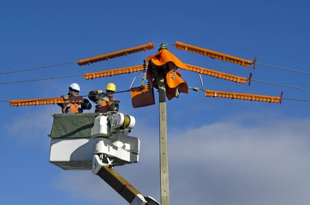 increasingly: MANGONUI,NZ - JUNE 11:Electrical workers repairs power pole on June 11 2013.NZ electricity sector uses mainly renewable energy sources such as hydro power,geothermal power and increasingly wind energy Editoriali