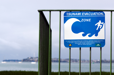 tsunami wave: AUCKLAND,NZ - MAY 30:Tsunami evacuation route sign on May 30 2013.A seabed earthquake along numerous stretches of the NZ coast can put a 10m-high tsunami wave within minutes to reach the coast ashore.