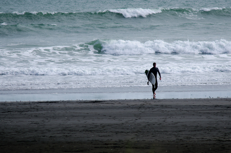 discovered: PIHA, NZ - JUNE 01: Wave surfer in Piha beach near Auckland on June 01 2013. Surfing was originated by the oceanic culture island of Polynesia and was first discovered by Captain Cook in 1778.