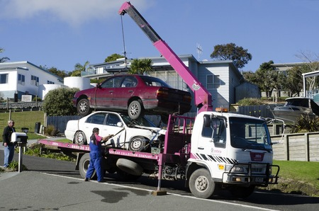 tow: CABLE BAY,NZ - JULY 01:Man towing damaged car over a tow truck on July 01 2013.The tow truck was invented in 1916 by Ernest Holmes,of Chattanooga, Tennessee. Editorial
