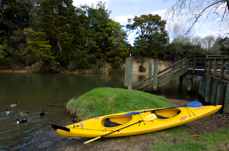 bank activities: MATAKANA, NZ - JUNE 02: A Kayak on Matakana river bank on June 02 2013.Because of their range and adaptability, kayaks can be useful also for other outdoor activities such as diving, fishing, wilderness exploration and search and rescue during floods.
