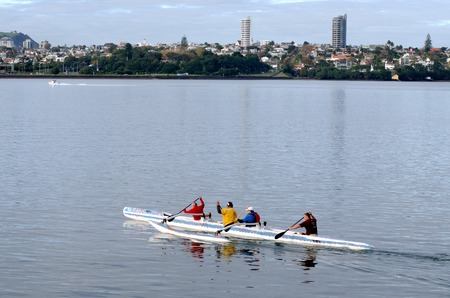 outrigger: AUCKLAND, NZ - JUNE 02:Crew of a racing outrigger canoe training in Waitemata Harbour on June 02 2013. It become a very popular paddling sport with numerous sporting clubs located around the world.