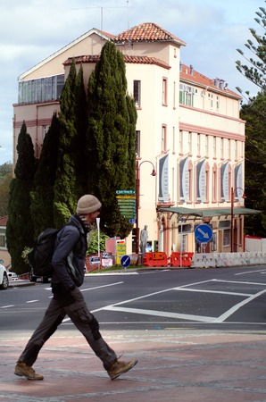 nz: TITIRANGI,NZ - JUNE 01:Traveler cross the main road of Titirangi on June 01 2013.The township is home to a number of New Zealand musicians, artists, writers and potters.
