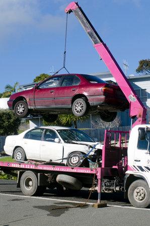 """camion grua: Cable Bay, Nueva Zelanda - JULY 01: Hombre de remolque dañada coche en grúa el día 01 Julio 2013.In Australia existe una Ley de grúa, camiones de remolque y se identifican por números de matrícula que terminan en """"TT"""" en varios estados. Editorial"""