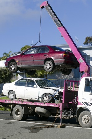 lift truck: CABLE BAY,NZ - JULY 01:Man towing damaged car on tow truck on July 01 2013.In Australia exists a Tow Truck Act, and tow trucks are identified by number plates ending in TT in several states. Editorial