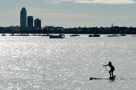 distances: AUCKLAND, NZ - JUNE 02:Silhouette of a person on SUP over Waitemata Harbour on June 02 2013.Its an emerging global sport with a Hawaiian heritage.Its an ancient form of surfing for longer distances.