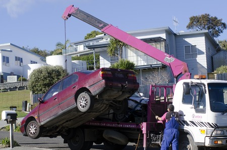 CABLE BAY,NZ - JULY 01:Man towing damaged car over a tow truck on July 01 2013.Many tow companies have the capability to store vehicles that have been wrecked or impounded by police agencies.