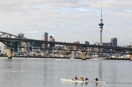 outrigger: AUCKLAND, NZ - JUNE 02:Crew of a racing outrigger canoe training against Auckland skyline on June 02 2013. It become a very popular paddling sport with numerous sporting clubs located around the world. Editorial