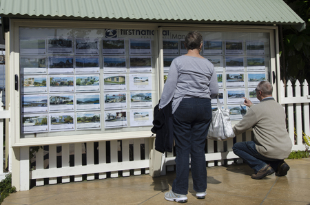 listing: MANGONUI,NZ - AUG 24:Couple looks at house listing on a signpost of Real Estate office on Aug 24 2013.NZ house prices are booming with the average price of an Auckland city home rocketing to $735,692. Editorial